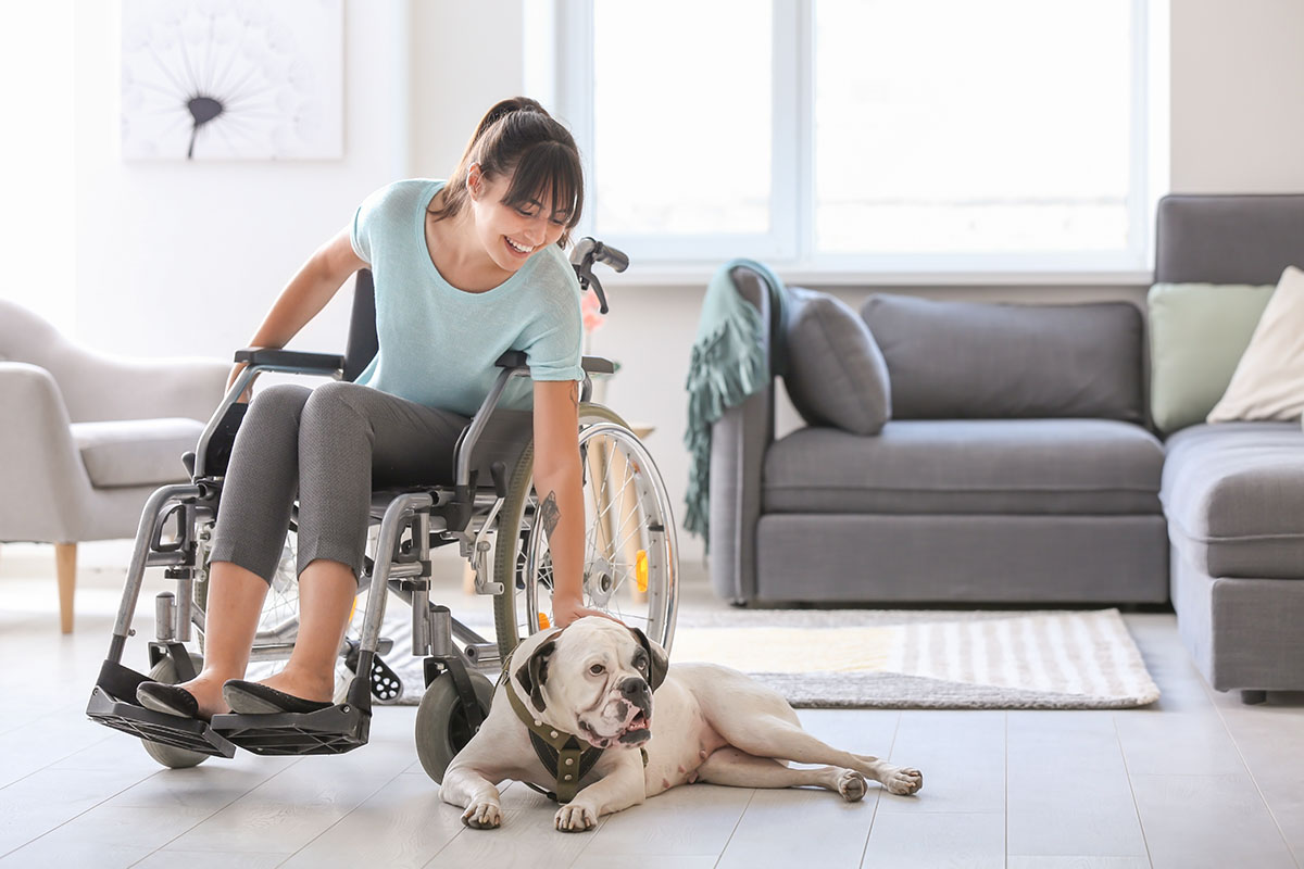 Woman in wheelchair petting her dog laying on living room floor