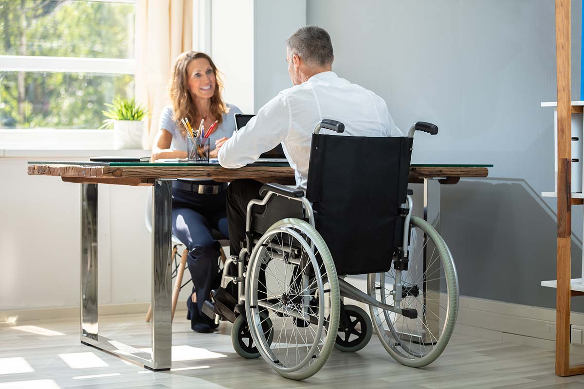 Man in wheelchair sitting at table meeting with a therapist